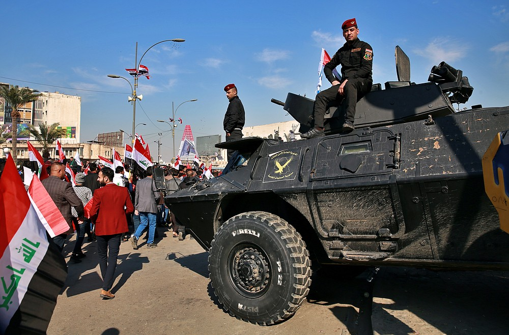 Security forces stand guard while supporters of Popular Mobilization Forces protest, in Tahrir Square, Iraq, Sunday, Jan. 3, 2021. Thousands of Iraqis converged on a landmark central square in Baghdad on Sunday to commemorate the anniversary of the killing of Abu Mahdi al-Muhandis, deputy commander of the Popular Mobilization Forces, and General Qassem Soleimani, head of Iran's Quds force in a U.S. drone strike. (AP Photo/Khalid Mohammed)