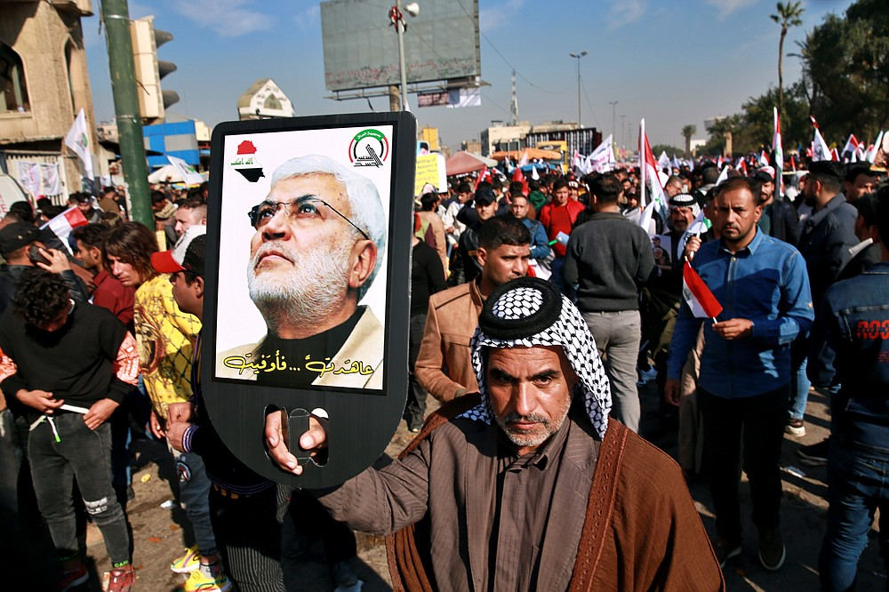 A supporter of Abu Mahdi al-Muhandis, deputy commander of the Popular Mobilization Forces, holds a photo of him during a protest in Tahrir Square, Iraq, Sunday, Jan. 3, 2021. Thousands of Iraqis converged on a landmark central square in Baghdad on Sunday to commemorate the anniversary of the killing of General Qassem Soleimani, head of Iran's Quds force and al-Muhandis in a U.S. drone strike. (AP Photo/Khalid Mohammed)
