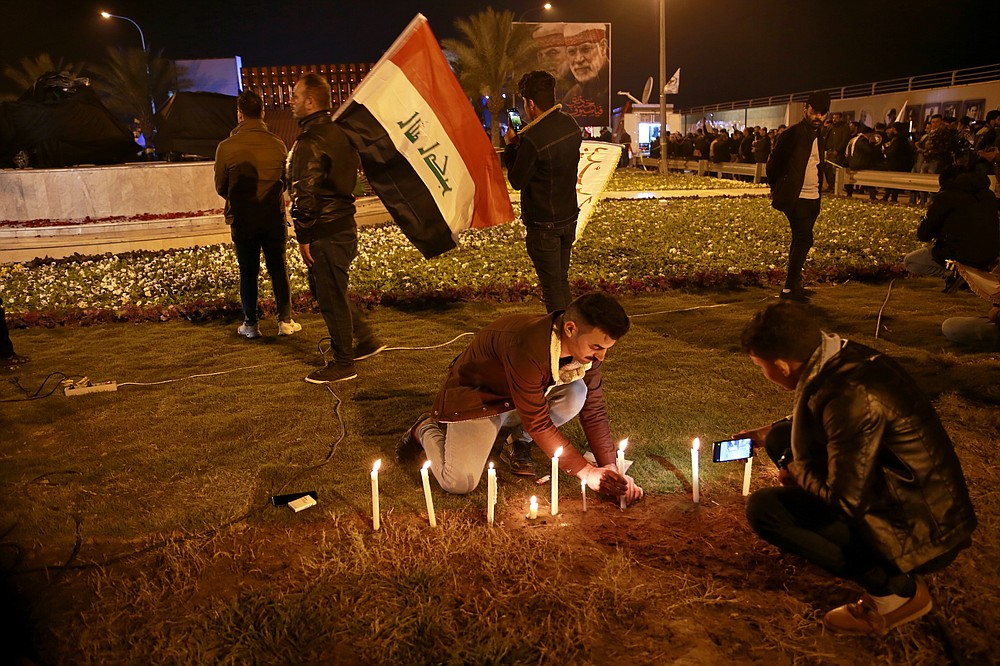 Popular Mobilization Forces and their supporters light candles at Baghdad's international airport on Saturday, Jan. 2, 2021, on the anniversary of the killing of Abu Mahdi al-Muhandis, deputy commander of the PMF and Gen. Qassem Soleimani, head of Iran's Quds forces in a U.S. airstrike. (AP Photo/Khalid Mohammed)