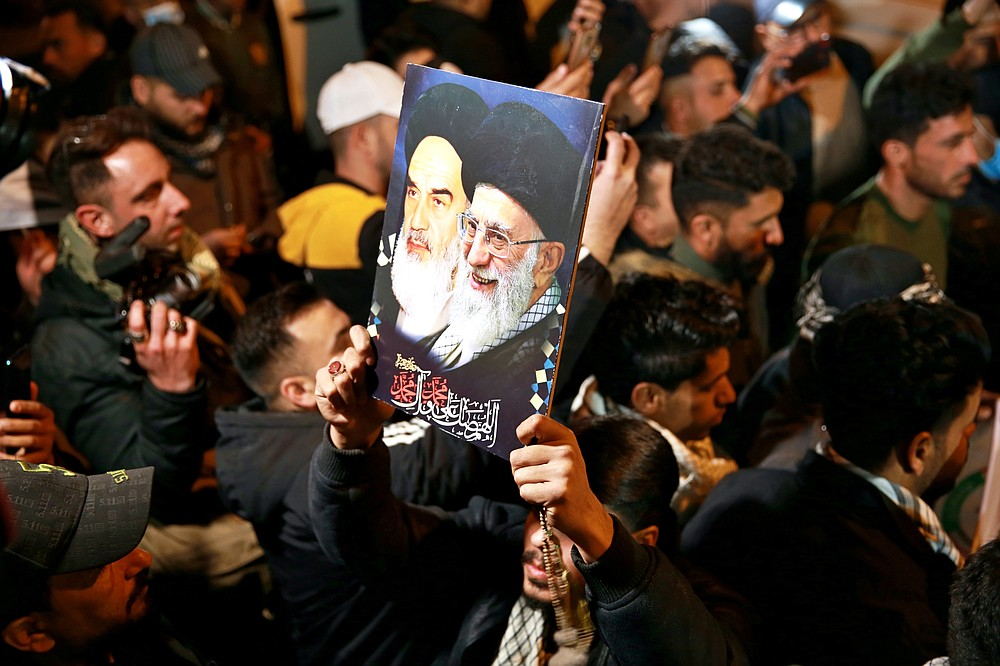 Members of the Popular Mobilization Forces (PMF) and their supporters chant slogans against the United States at Baghdad's international airport on Saturday, Jan. 2, 2021, for the anniversary of the killing of Abu Mahdi al-Muhandis, deputy commander of the PMF, and Gen. Qassem Soleimani, head of Iran's Quds Force in a U.S. airstrike. The poster depicting late Iranian revolutionary founder Ayatollah Khomeini, left, and Supreme Leader Ayatollah Ali Khamenei. (AP Photo/Khalid Mohammed)