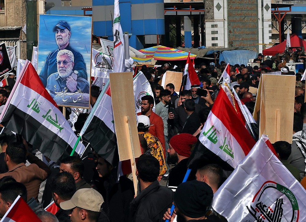Supporters of the Popular Mobilization Forces hold a poster of Abu Mahdi al-Muhandis, deputy commander of the Popular Mobilization Forces, front, and General Qassem Soleimani, head of Iran's Quds force during a protest, in Tahrir Square, Iraq, Sunday, Jan. 3, 2021. Thousands of Iraqis converged on a landmark central square in Baghdad on Sunday to commemorate the anniversary of the killing of Soleimanil and al-Muhandis in a U.S. drone strike. (AP Photo/Khalid Moha