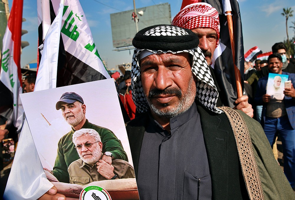 Supporters of the Popular Mobilization Forces hold a posters of Abu Mahdi al-Muhandis, deputy commander of the Popular Mobilization Forces, front, and General Qassem Soleimani, head of Iran's Quds force during a protest, in Tahrir Square, Iraq, Sunday, Jan. 3, 2021. Thousands of Iraqis converged on a landmark central square in Baghdad on Sunday to commemorate the anniversary of the killing of Soleimanil and al-Muhandis in a U.S. drone strike. (AP Photo/Khalid Mohammed)