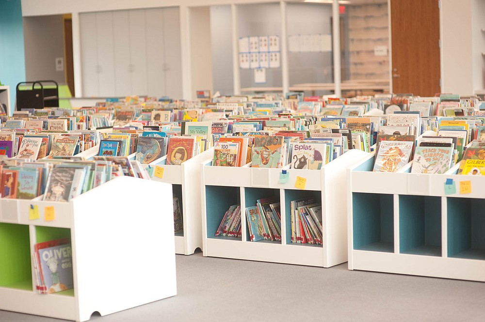 Hererra says the library has added more than 100,000 new items during the course of the expansion. The increase is especially obvious in the bins and bins of new books in the pre-school section of the Children's Library.  (NWA Democrat-Gazette/Lara Jo Hightower)