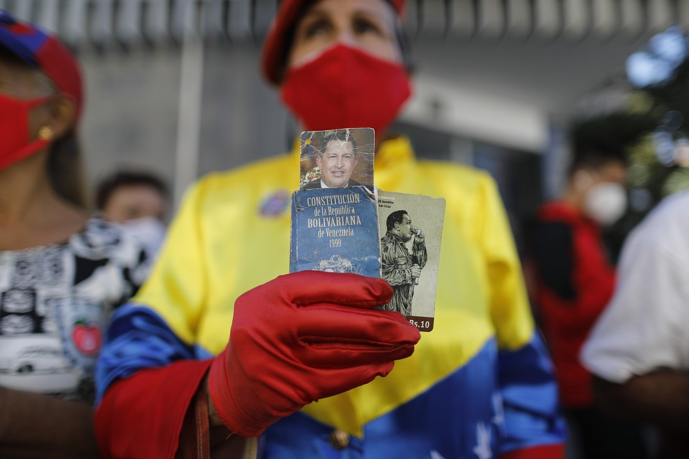 A government supporter Julia Mercedes Gutierrez holds photos of late Venezuelan President Hugo Chavez and a small version of the national constitution outside the National Assembly where lawmakers are being sworn-in, in Caracas, Venezuela, Tuesday, Jan. 5, 2021. The ruling socialist party assumed the leadership of Venezuela's congress on Tuesday, the last institution in the country it didn't already control. (AP Photo/Ariana Cubillos)