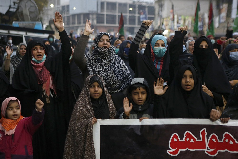 Shiite Muslims chant slogans during a sit-in to protest the killing of coal mine workers by gunmen near the Machh coal field, in Lahore, Pakistan, Wednesday, Jan. 6, 2021. Pakistan's minority Shiites continued their sit-in for a fourth straight day insisting they will bury their dead only when Prime Minister Imran Khan personally visits them to assure protection. (AP Photo/K.M. Chaudary)