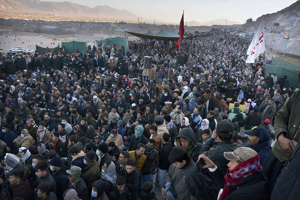 People from the Shiite Hazara community hold a sit-in to protest the killing of coal mine workers by gunmen near the Machh coal field, in Quetta, Pakistan, Wednesday, Jan. 6, 2021. Pakistan's minority Shiites continued their sit-in for a fourth straight day on the outskirts of the southwestern city of Quetta to protest the killing Sunday of 11 coal miners by the Islamic State group, insisting they will bury their dead only when Prime Minister Imran Khan personally visits them to assure protection. (AP Photo/Arshad Butt)