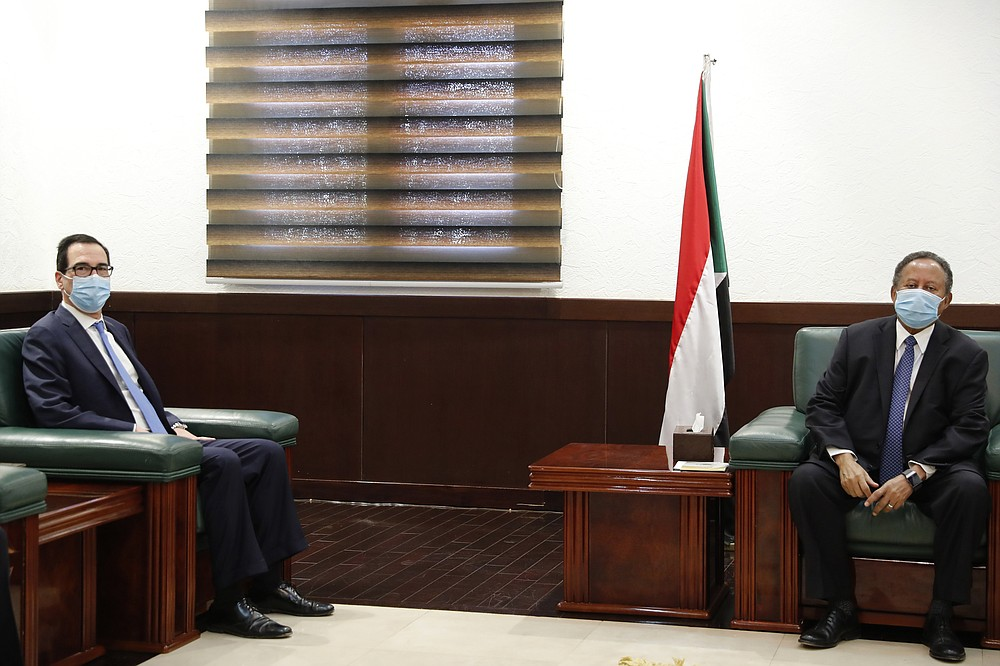 Sudanese Prime Minister Abdullah Hamdok, right, meets with US Treasury Secretary Steven Mnuchin in the Cabinet Building, in Khartoum, Sudan, Wednesday, Jan. 6, 2021. The U.S. and Sudan have agreed to settle the African country's debt to the World Bank. The move comes after Mnuchin arrived in Sudan, the first visit by a senior American official since President Donald trump removed Sudan from the list of state sponsors of terrorism. (AP Photo)