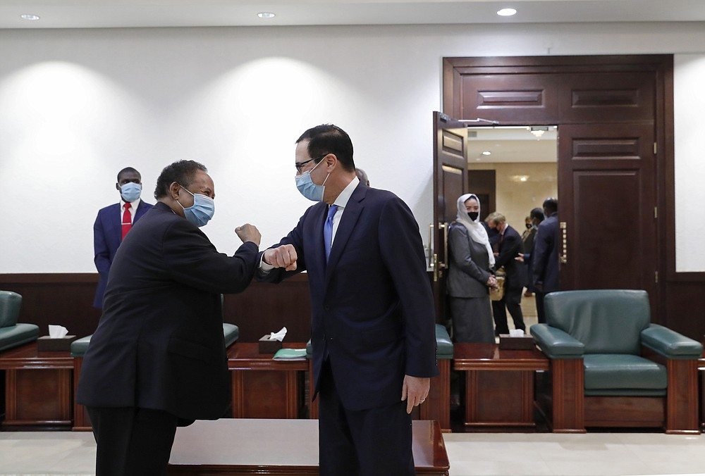 Sudanese Prime Minister Abdullah Hamdok, left, elbow bumps as he welcomes US Treasury Secretary Steven Mnuchin to the Cabinet Building, in Khartoum, Sudan, Wednesday, Jan. 6, 2021. The U.S. and Sudan have agreed to settle the African country's debt to the World Bank. The move comes after Mnuchin arrived in Sudan, the first visit by a senior American official since President Donald trump removed Sudan from the list of state sponsors of terrorism. (AP Photo)
