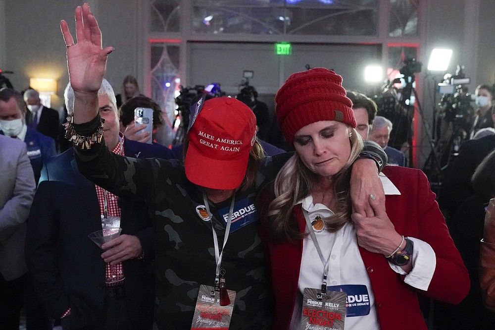 Two women pray during a Republican election-night watch party, Tuesday, Jan. 5, 2021, in Atlanta. (AP Photo/John Bazemore)