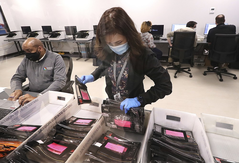 Election workers tabulate ballots at the Beauty P. Baldwin Voter Registrations and Elections Building, Tuesday, Jan. 5, 2021, in Lawrenceville, Ga. (Curtis Compton/Atlanta Journal-Constitution via AP)