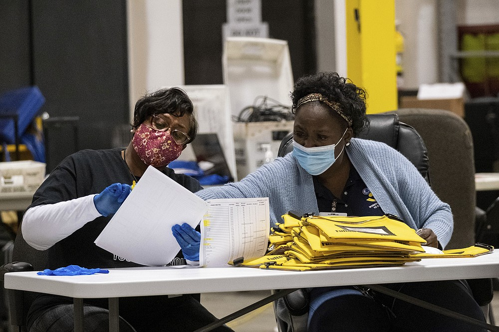 Elections workers at the Fulton County Georgia elections warehouse check in voting machine memory cards that store ballots following the Senate runoff election in Atlanta on Tuesday, Jan. 5, 2021. Georgia's two Senate runoff elections on Tuesday will determine which party controls the U.S. Senate. Republican Kelly Loeffler is going up against Democrat Raphael Warnock, while Republican David Perdue is challenging Democrat Jon Ossoff. Democrats must win both seats to take control of the Senate. (AP Photo/Ben Gray)