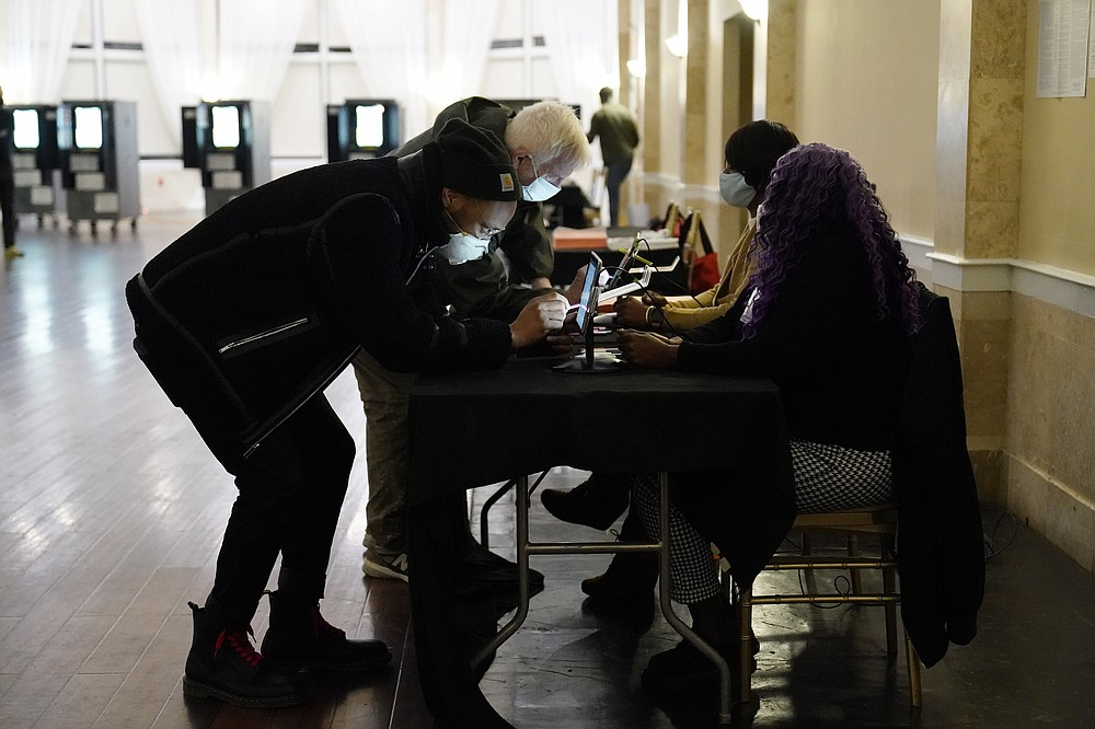 Voters register before casting their vote during Georgia's Senate runoff elections on Tuesday, Jan. 5, 2021, in Atlanta. (AP Photo/Brynn Anderson)