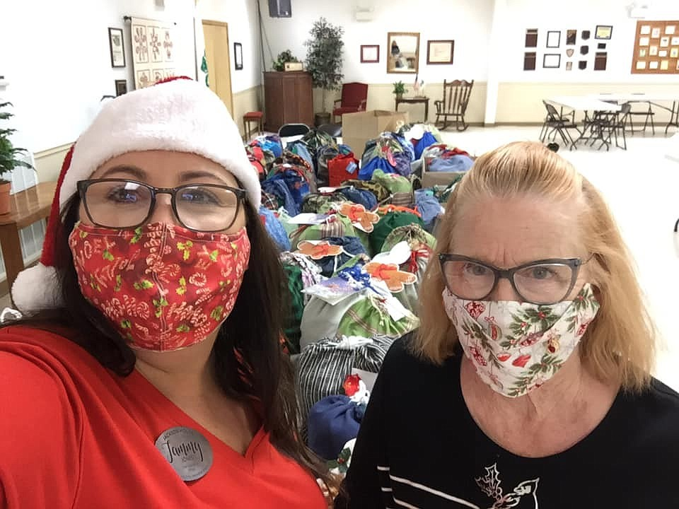 Tammy Jones with Jackson House receives 105 drawstring bags made and filled by Garland County Extension Homemakers members for tweens and teens served by the Jackson House family Christmas program from Rita Blackwood. - Submitted photo
