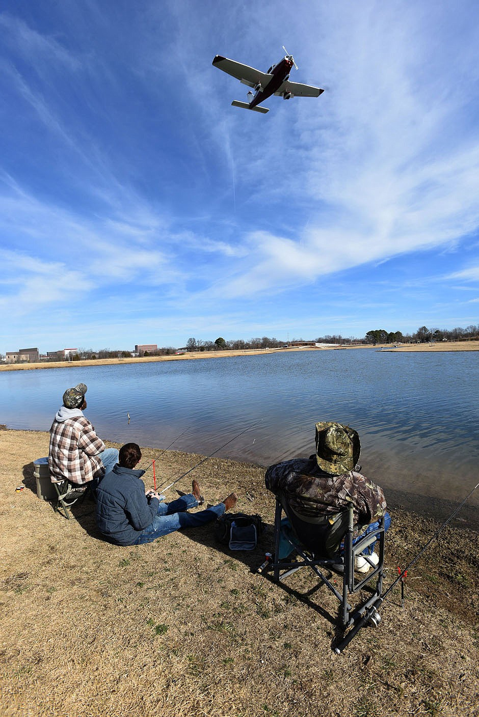 Anglers watch airplanes land while fishing for trout on Dec. 26 2020 at Lake Bentonville. The lake hugs the runway on the north side of the airport. (NWA Democrat-Gazette/Flip Putthoff)