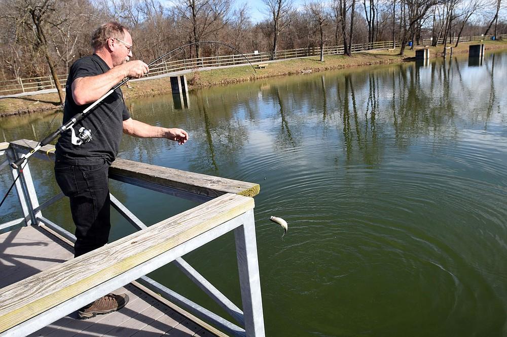 Joe Needham of Fayetteville lands a trout Dec. 26 2020 he caught with Power Bait at Lake Springdale. (NWA Democrat-Gazette/Flip Putthoff)