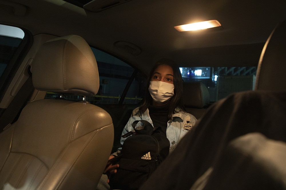 Sara leaves Ezeiza airport in a car upon arrival to Buenos Aires, Argentina, Sunday, Dec. 13, 2020, after flying in from Brazil. Brazilian women without means have started seeking abortions elsewhere in Latin America to dodge risks and legal obstacles in the region's most populous country. (AP Photo/Emiliana Miguelez)
