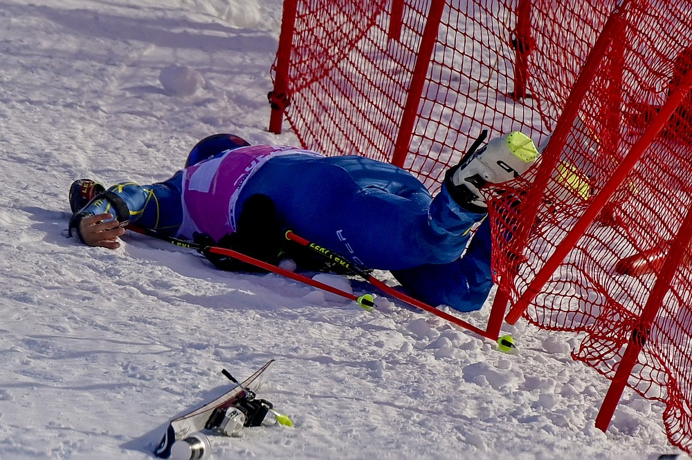 Injured Tommy Ford lies in the net during the first run of the men's giant slalom race at the FIS Alpine Skiing World Cup in Adelboden, Switzerland, Saturday, Jan. 9, 2021. (Jean-Christophe Bott/Keystone via AP)