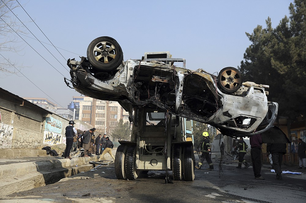 Afghan security personnel remove a damaged vehicle after a bomb attack in Kabul, Afghanistan, Sunday, Jan. 10, 2021. A roadside bomb exploded in Afghanistan's capital Sunday, killing at least a few people in a vehicle, the latest attack to take place even as government negotiators are in Qatar to resume peace talks with the Taliban. (AP Photo/Rahmat Gul)