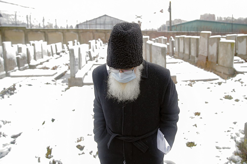 Rabbi Rafael Schaffer wears a face mask to protect against coronavirus, during the funeral of Iancu Tucarman, at a Jewish cemetery in Bucharest, Romania, Monday, Jan. 11, 2021. Tucarman, one of the last remaining Holocaust survivors in Romania, on was buried after dying from COVID-19 last week at the age of 98. (AP Photo/Vadim Ghirda)