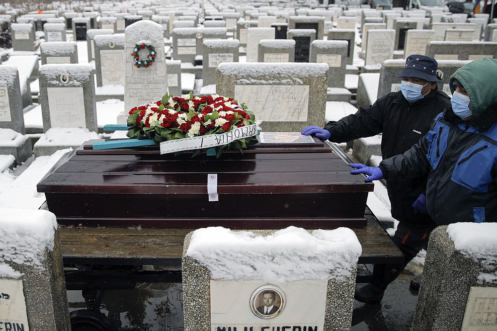 The coffin of Iancu Tucarman is is transported on a cart, to the burial plot, at a Jewish cemetery in Bucharest, Romania, Monday, Jan. 11, 2021. Tucarman, one of the last remaining Holocaust survivors in Romania, on was buried after dying from COVID-19 last week at the age of 98. (AP Photo/Vadim Ghirda)