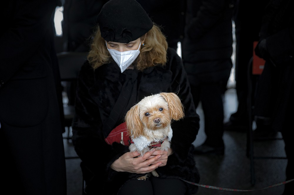 Maria Popa the partner of Iancu Tucarman holds Lady, the family dog, during his funeral, at a Jewish cemetery in Bucharest, Romania, Monday, Jan. 11, 2021. Tucarman, one of the last remaining Holocaust survivors in Romania, on was buried after dying from COVID-19 last week at the age of 98. (AP Photo/Vadim Ghirda)
