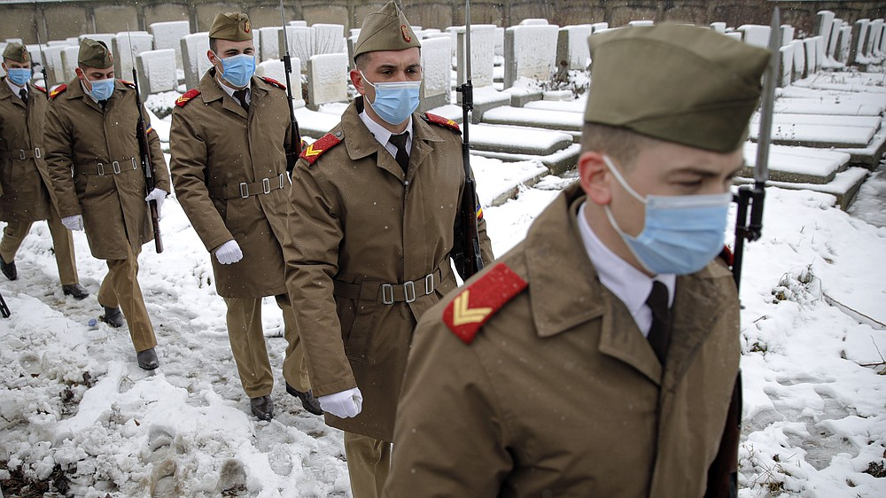 Honor guard soldiers walk by graves before the funeral of Iancu Tucarman, at a Jewish cemetery in Bucharest, Romania, Monday, Jan. 11, 2021. Tucarman, one of the last remaining Holocaust survivors in Romania, on was buried after dying from COVID-19 last week at the age of 98. (AP Photo/Vadim Ghirda)