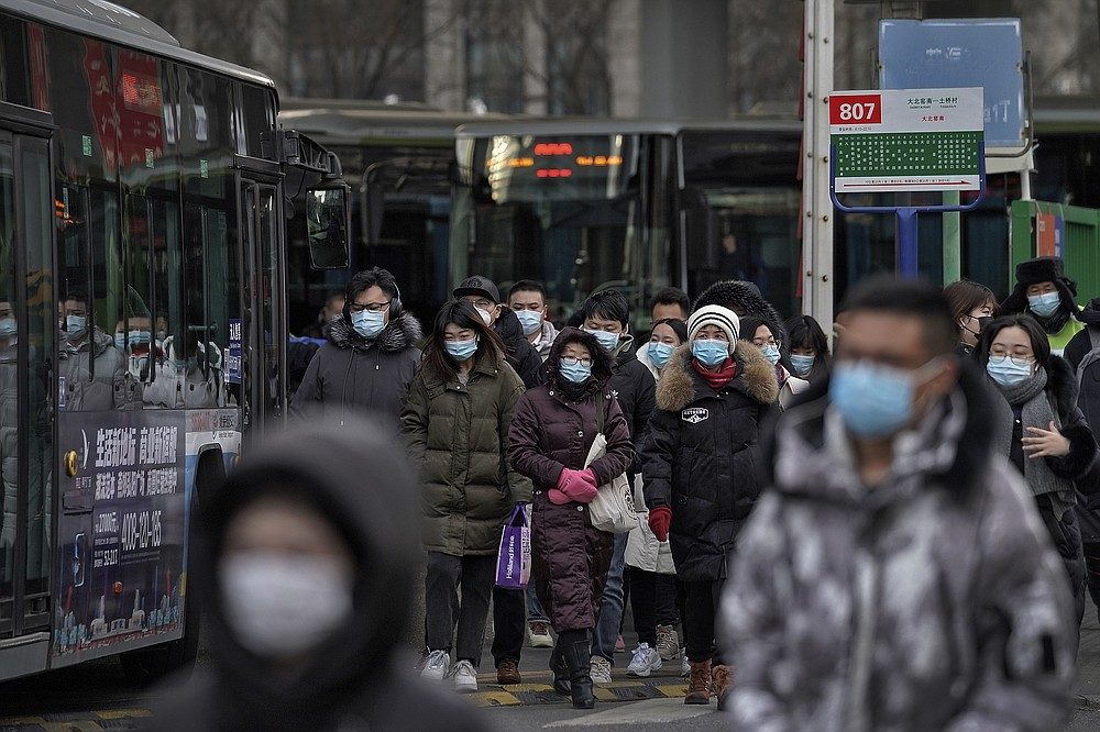 People wearing face masks to help curb the spread of the coronavirus walk out from a bus station for the traveller from the outskirts of Beijing on Monday, Jan. 11, 2012. Chinese health authorities say scores more people have tested positive for coronavirus in Hebei province bordering on the capital Beijing. The outbreak focused on the Hebei cities of Shijiazhuang and Xingtai is one of China's most serious in recent months and comes amid measures to curb the further spread during next month's Lunar New Year holiday. (AP Photo/Andy Wong)