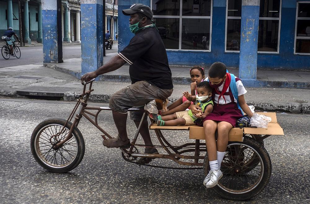 A man transports children on his tricycle, in Havana, Cuba, Friday, Jan 8, 2021, amid the new coronavirus pandemic. (AP Photo/Ramon Espinosa)