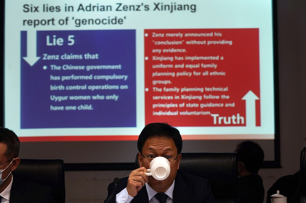 "Xu Guixiang, a deputy spokesperson for the Xinjiang regional government, drinks from a cup near a slide refuting claims of genocide during a press conference in Beijing, China. The Chinese official on Monday denied Beijing has imposed coercive birth control measures among Muslim minority women, following an outcry over a tweet by the Chinese Embassy in Washington claiming that government polices had freed women of the Uighur ethnic group from being ""baby-making machines."" (AP Photo/Ng Han Guan)"