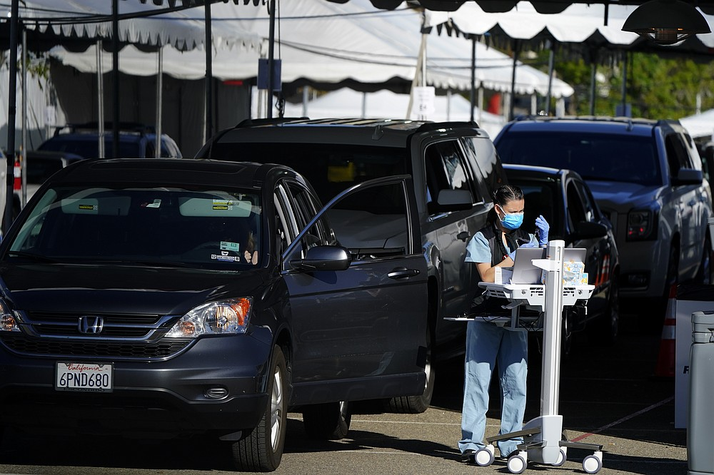 "People wait in cars for a vaccination against the coronavirus at a new ""vaccination superstation,"" Monday, Jan. 11, 2021, in San Diego. The site, which opened Monday, began providing large-scale COVID-19 vaccinations to health care workers. The U.S. is entering the second month of the biggest vaccination effort in history with a major expansion of the campaign, opening football stadiums, major league ballparks, fairgrounds, and convention centers to inoculate a larger and more diverse pool of people. (AP Photo/Gregory Bull)"
