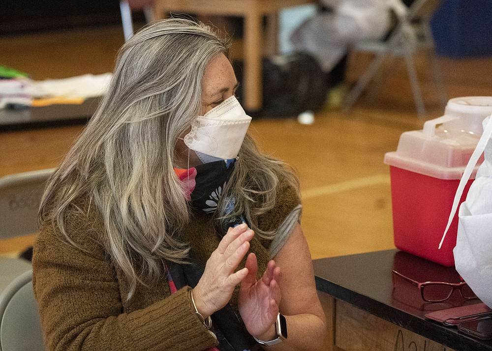 "Teacher Lisa Egan claps after she receives the Moderna coronavirus vaccine at a clinic organized by New York City's Department of Health, Monday, Jan. 11, 2021. ""I feel so great, so lucky,"" she said. ""I've been teaching remotely. I'm hoping now I can go back to the classroom."" Monday was the first day that people over 75 and essential workers — including police officers, firefighters, and teachers — were allowed to receive the vaccines in New York. (AP Photo/Mark Lennihan)"