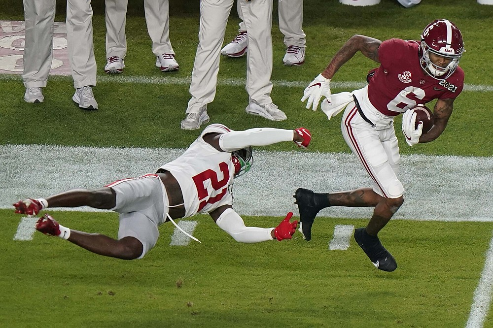 Alabama wide receiver DeVonta Smith runs past Ohio State cornerback Marcus Williamson during the first half of an NCAA College Football Playoff national championship game, Monday, Jan. 11, 2021, in Miami Gardens, Fla. (AP Photo/Wilfredo Lee)