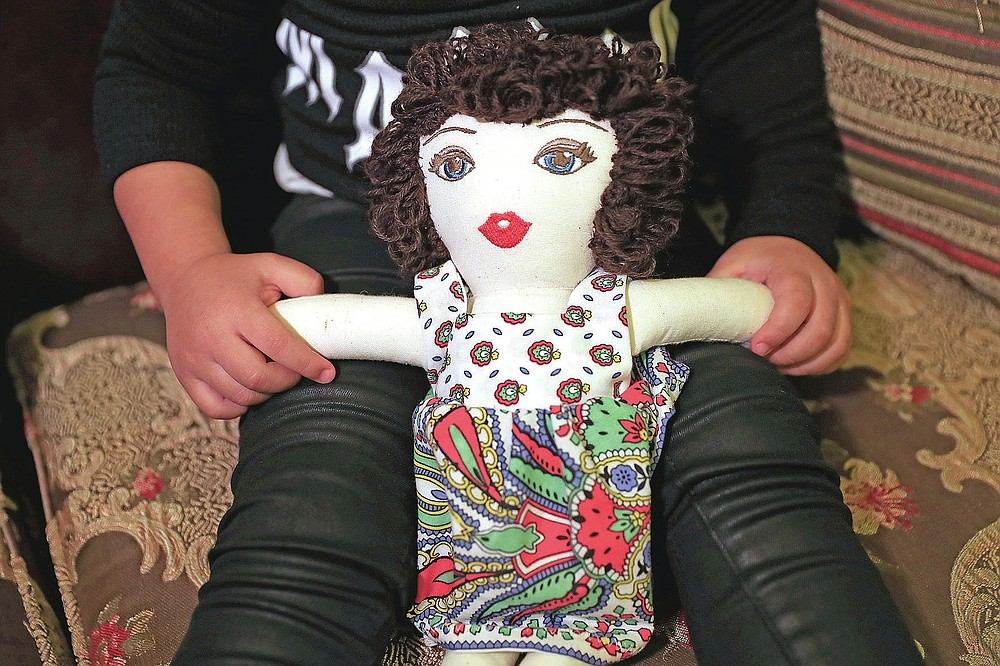Sima-Rita, whose family home had the windows blown out during August's massive explosion in Beirut, holds her doll at her grandfather's home, in Beirut, Lebanon, Tuesday, Dec. 29, 2020. After the explosion, painter Yolande Labaki made 100 dolls for children affected by the destruction. (AP Photo/Hussein Malla)