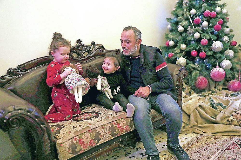 Georges Chlawuit, right, sits with his daughters Sama, 2, left, and Sima-Rita, 3, center, as they play with dolls at a relative's home, in Beirut, Lebanon, Tuesday, Dec. 29, 2020. In August, the massive explosion in Beirut blew out the windows of their family home. Painter Yolande Labaki made 100 dolls for children affected by the destruction. (AP Photo/Hussein Malla)