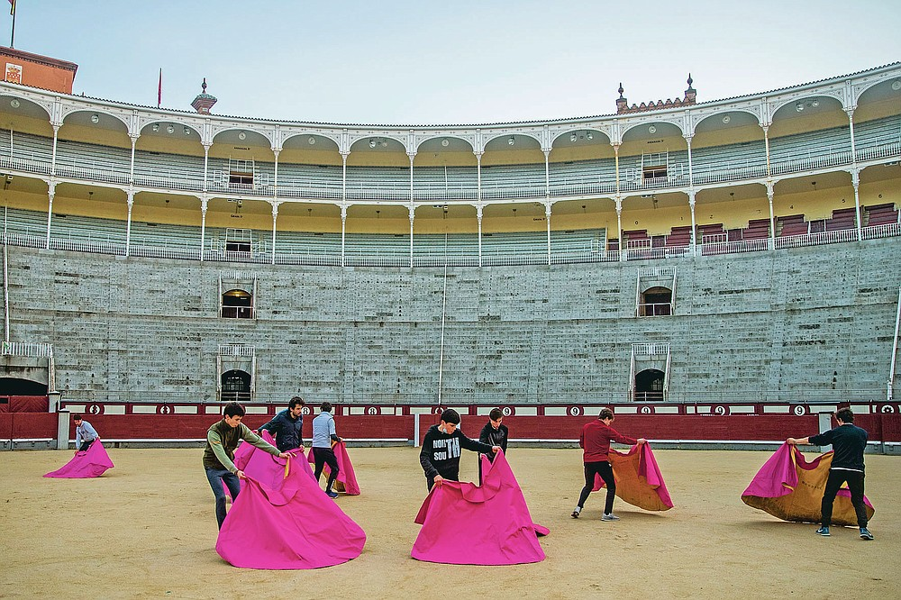 Pupils perform with their capes at the Bullfighting School at Las Ventas bullring in Madrid, Spain, Tuesday, Dec. 22, 2020. The school was closed from March to August when Spain went into one of the world's strictest confinements to stem the spread of the COVID-19 pandemic. (AP Photo/Manu Fernandez)