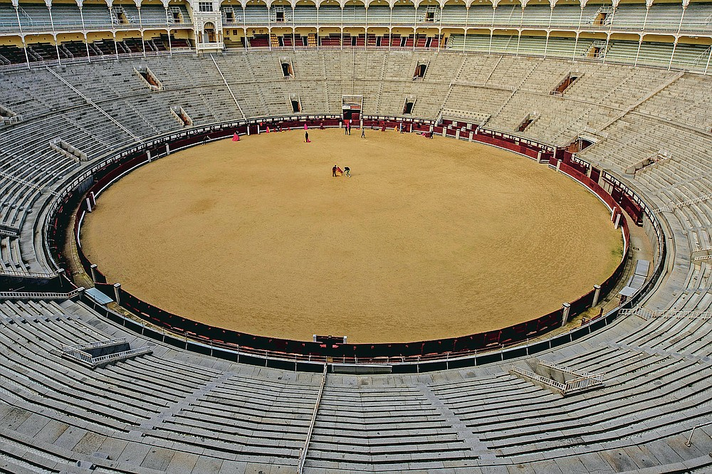Pupils practice with their capes at the Bullfighting School at Las Ventas bullring in Madrid, Spain, Tuesday, Dec. 29, 2020. One boy practices making an elegant swivel with his cape outstretched as his fellow pupil slowly sweeps past with a pair of bull horns held in front. (AP Photo/Manu Fernandez)