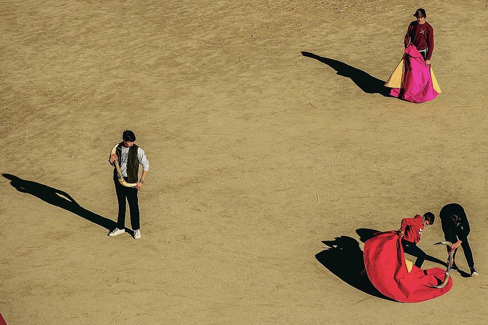 Pupils practice with their capes at the Bullfighting School at Las Ventas bullring in Madrid, Spain, Tuesday, Dec. 29, 2020. Holding the red cape outstretched, one boy practices making an elegant swivel as his fellow pupil slowly sweeps past with a pair of bull horns held in front. (AP Photo/Manu Fernandez)