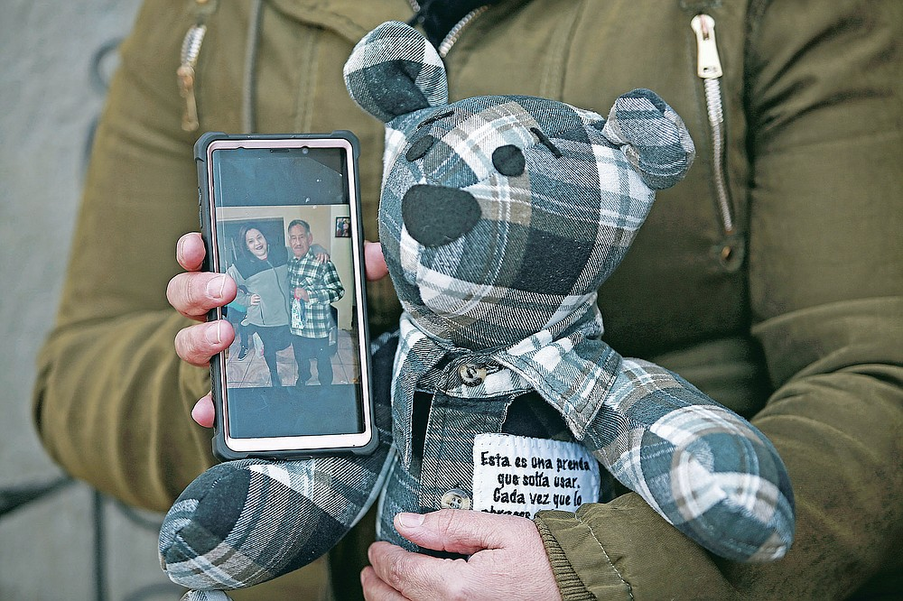 """Araceli Ramirez shows a stuffed bear she had made from the shirt of her father, Lorenzo Ramirez, who died so quickly from COVID-19 two months ago that she was unable to say goodbye, as she stands outside the home of bear maker Erendira Guerrero following a TV interview, in Ciudad Juarez, Mexico, Monday, Jan. 11, 2021. Ramirez, who had the bear made from a warm winter shirt her father loved, said """"I can talk to the bear, express what I didn't tell him, and feel like he is with me."""" (AP Photo/Christian Chavez)"""