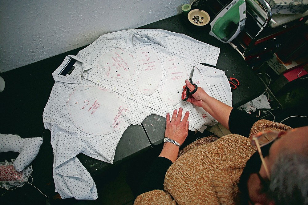 """Erendira Guerrero cuts pieces from the shirt of a person who died of COVID-19 as she makes a stuffed bear for one of the deceased's relatives, at her home workshop in Ciudad Juarez, Mexico, Monday, Jan. 11, 2021. """"Due to COVID-19, many people were left without closure, because they couldn't say goodbye to their family members. They need to close the circle. The bears are helping them,"""" said Guerrero. (AP Photo/Christian Chavez)"""