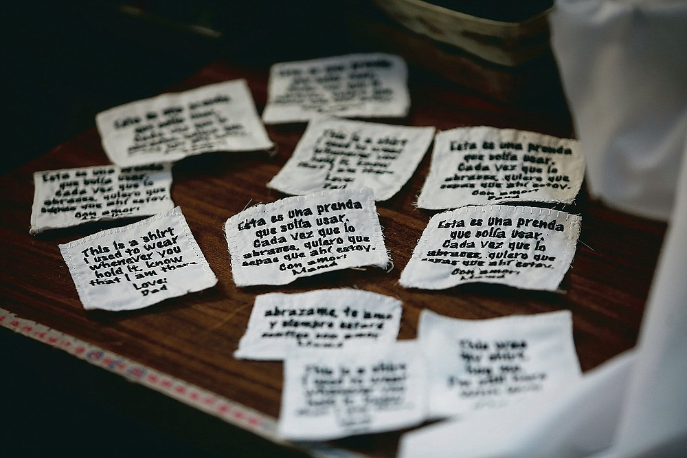 """Tags ready to be sewn onto bears made for people who lost a loved one to COVID-19, out of one of the deceased's articles of clothing, sit beside a sewing machine in the home workshop of Erendira Guerrero in Ciudad Juarez, Mexico, Monday, Jan. 11, 2021. """"Due to COVID-19, many people were left without closure, because they couldn't say goodbye to their family members. They need to close the circle. The bears are helping them,"""" said Erendira. (AP Photo/Christian Chavez)"""