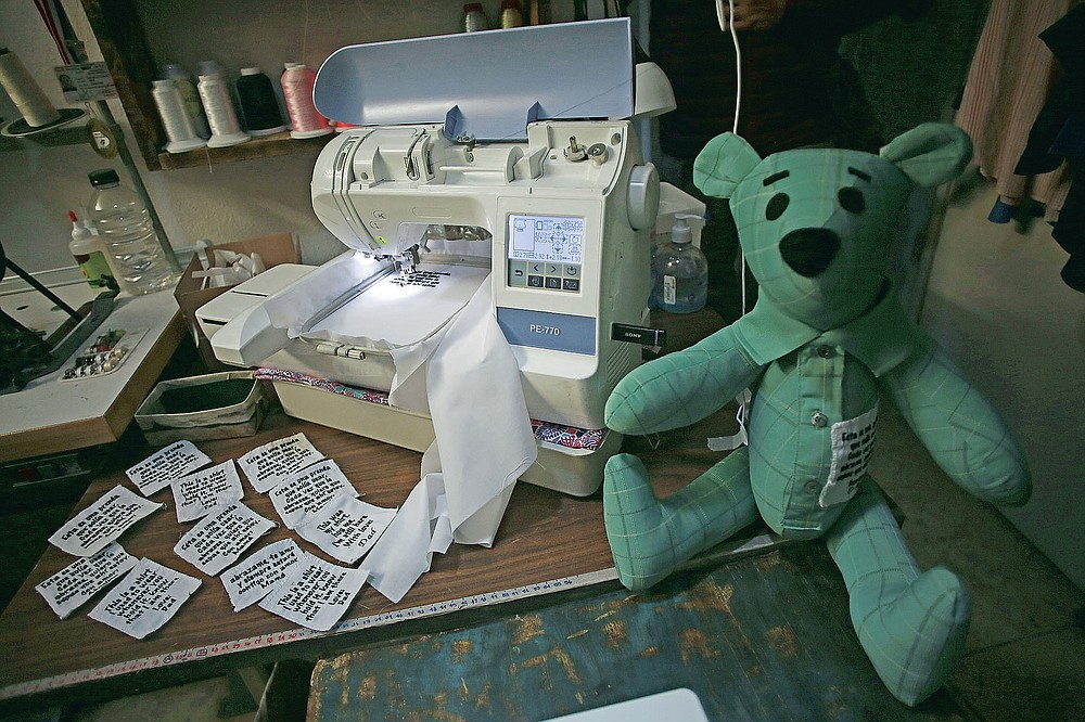 """Tags ready to be sewn onto bears for people who lost a loved one to COVID-19, made out of one of the deceased's articles of clothing, sit beside a sewing machine at the home workshop of Erendira Guerrero in Ciudad Juarez, Mexico, Monday, Jan. 11, 2021. """"Due to COVID-19, many people were left without closure, because they couldn't say goodbye to their family members. They need to close the circle. The bears are helping them,"""" said Erendira. (AP Photo/Christian Chavez)"""