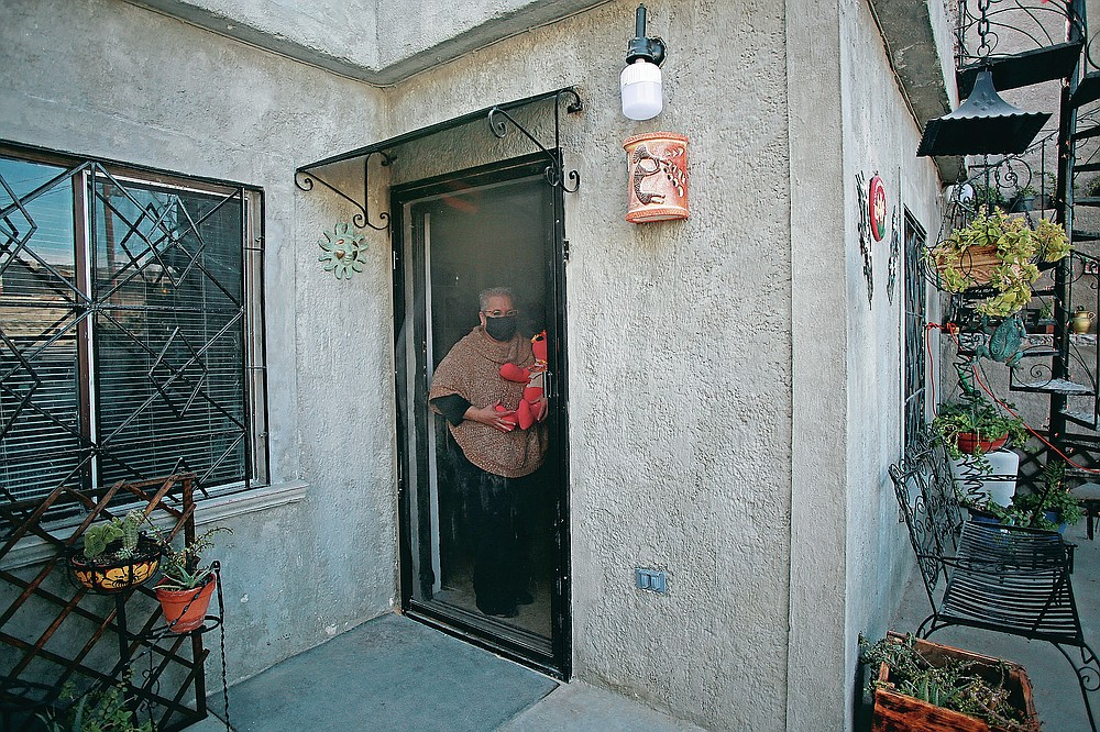 """Erendira Guerrero stands at the door of her home, holding one of the stuffed bears she makes for people who lost a family member to COVID-19, using one of the deceased's favorite articles of clothing, in Ciudad Juarez, Mexico, Monday, Jan. 11, 2021. """"Due to COVID-19, many people were left without closure, because they couldn't say goodbye to their family members. They need to close the circle. The bears are helping them,"""" said Guerrero. (AP Photo/Christian Chavez)"""