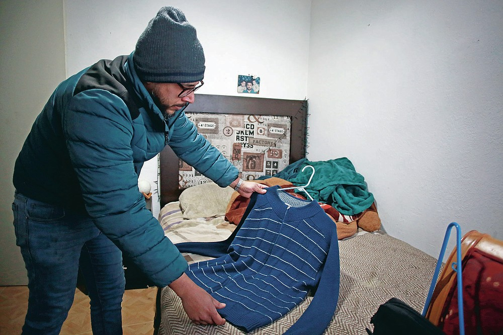 """Jaime Walfre Aguilar Martinez, whose 50-year-old father died of COVID-19 in November, selects one of his father's favorite sweaters to have a stuffed bear made from the fabric, at his home in Ciudad Juarez, Mexico, Monday, Jan. 11, 2021. Erendira Guerrero, who makes the bears in her home workshop, said, """"Due to COVID-19, many people were left without closure, because they couldn't say goodbye to their family members. They need to close the circle. The bears are helping them.""""(AP Photo/Christian Chavez)"""