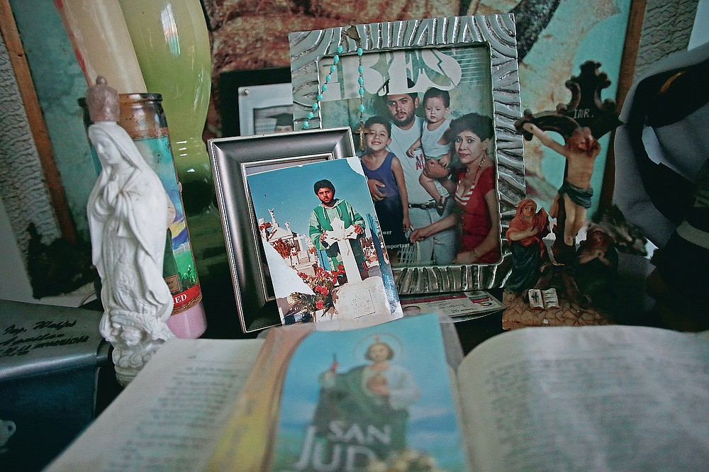 """Pictures of Jaime Aguilar Rojas, who was 50 when he died of COVID-19 in November, adorn an altar in the home of his son, Jaime Walfre Aguilar Martinez, who has decided to have a stuffed bear made from the fabric of his father's favorite sweater, in Ciudad Juarez, Mexico, Monday, Jan. 11, 2021. Erendira Guerrero, who makes the bears in her home workshop, said, """"Due to COVID-19, many people were left without closure, because they couldn't say goodbye to their family members. They need to close the circle. The bears are helping them.""""(AP Photo/Christian Chavez)"""