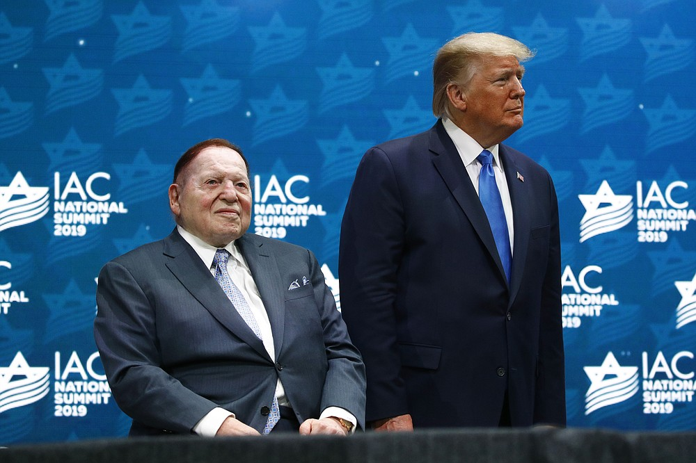 FILE - In this Dec. 7, 2019 file photo, President Donald Trump stands alongside Las Vegas Sands Corporation Chief Executive and Republican mega donor Sheldon Adelson before speaking at the Israeli American Council National Summit in Hollywood, Fla.   Adelson, the billionaire mogul and power broker who built a casino empire spanning from Las Vegas to China and became a singular force in domestic and international politics has died after a long illness, his wife said Tuesday, Jan. 12, 2021. (AP Photo/Patrick Semansky, File)