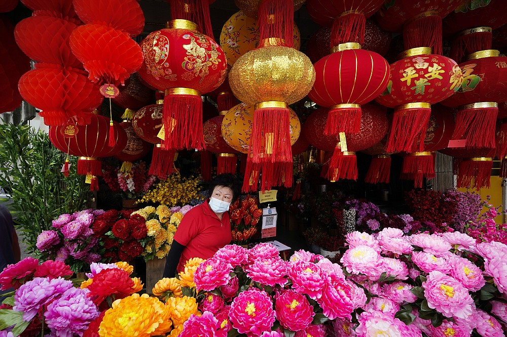 A woman wearing a face mask looks through Chinese New Year lantern decorations at a shop in Kuala Lumpur, Malaysia, Tuesday, Jan. 12, 2021. Malaysia's king Tuesday approved a coronavirus emergency that will prorogue parliament and halt any bids to seek a general election in a political reprieve for embattled Prime Minister Muhyiddin Yassin. (AP Photo/Vincent Thian)