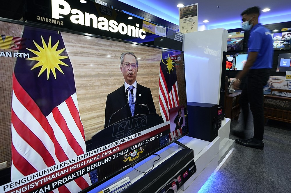 An electronic shop worker wearing a face mask walks near a television showing a live broadcast of Malaysian Prime Minister Muhyiddin Yassin at a shopping outlet in Kuala Lumpur, Malaysia, Tuesday, Jan. 12, 2021. Malaysia's king Tuesday approved a coronavirus emergency that will prorogue parliament and halt any bids to seek a general election in a political reprieve for embattled Muhyiddin. (AP Photo/Vincent Thian)