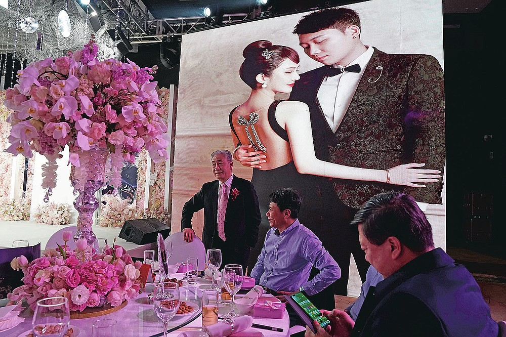 Family and guests attend the wedding banquet for Chen Yaxuan and Dou Di in Beijing on Saturday, Dec. 12, 2020. Lovebirds in China are embracing a sense of normalcy as the COVID pandemic appears to be under control in the country where it was first detected. (AP Photo/Ng Han Guan)