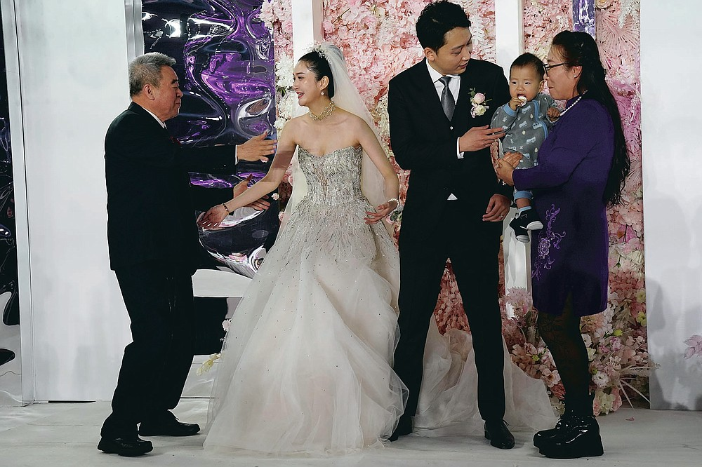 Bride Chen Yaxuan and groom Dou Di greet guests during a wedding banquet in Beijing on Saturday, Dec. 12, 2020. Lovebirds in China are embracing a sense of normalcy as the COVID pandemic appears to be under control in the country where it was first detected. (AP Photo/Ng Han Guan)