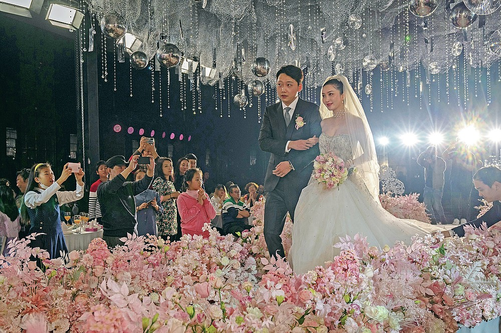 Bride Chen Yaxuan and groom Dou Di walk down the stage during an unmasked wedding banquet in Beijing on Saturday, Dec. 12, 2020. Lovebirds in China are embracing a sense of normalcy as the COVID pandemic appears to be under control in the country where it was first detected. (AP Photo/Ng Han Guan)